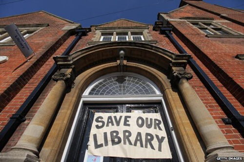 Save our Libraries banner hanging over the entrance of a library image