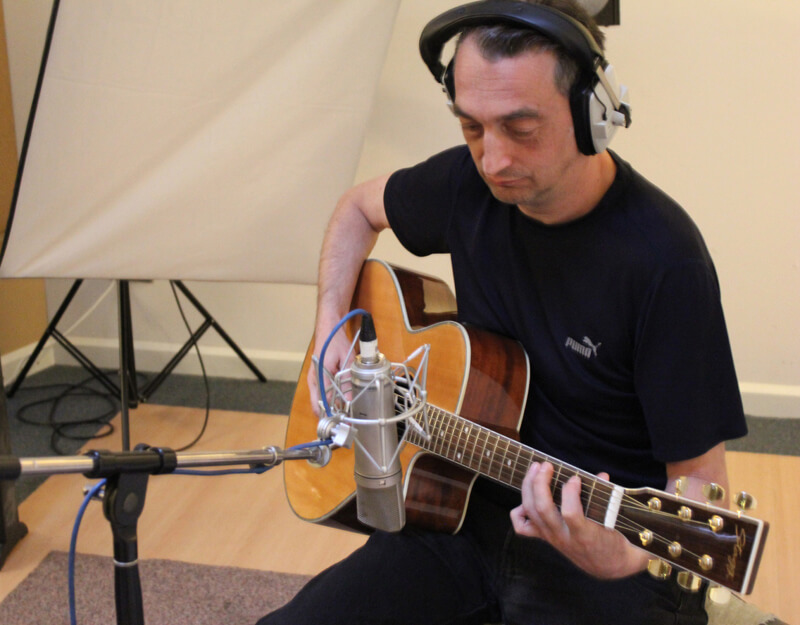 Adie Hardy recording acoustic guitar in one of our Music Audio Stories image