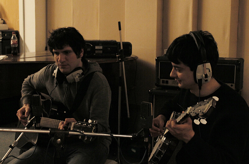 Aris Tsigaras and Aaron John recording guitar and banjo for their song in the studio
