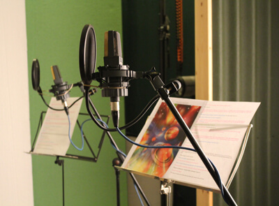 The script for the story and a photo of the Solar System with microphones in the studio image