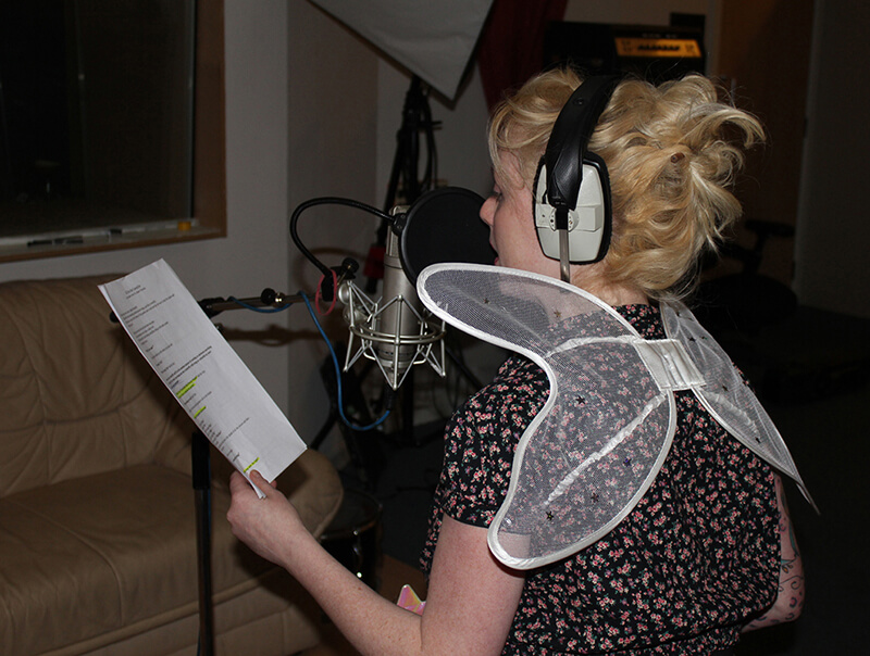 Kiria Ceinwen with fairy wings, recording Butterfly the fairy in audiobook Chris the Caterpillar by Music Audio Stories